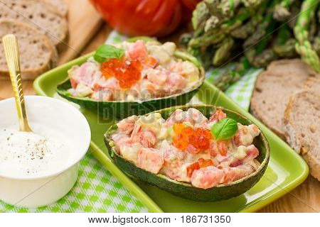 Stuffed avocado with tomato garlic and mayonnaise served with salmon roe