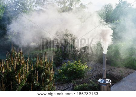 Smoke from a samovar pipe on backyard of country house in summer evening
