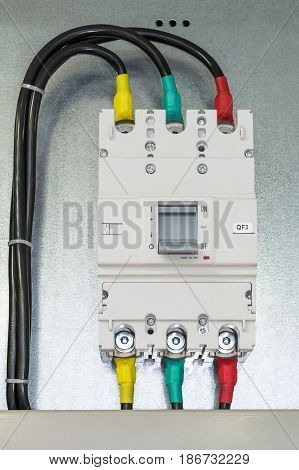 On a mounting plate or Board fixed power circuit breaker. Connected electrical cables in insulation top and bottom. The handle of the circuit breaker in the off position.