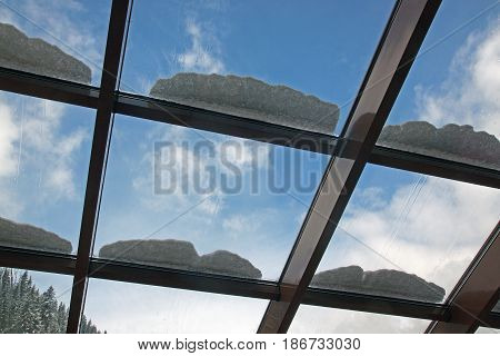 Glass ceiling in a cafe. Sprinkle with snow against the blue sky