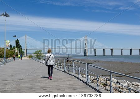 LISBON, PORTUGAL - APRIL 27: Walkway by the Tajo river and the Vasco da Gama Bridge in Lisbon Portugal  on April 27, 2017