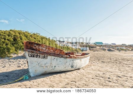 PATERNOSTER SOUTH AFRICA - APRIL 1 2017: View of a fishing boat and houses at a beach in Paternoster a small town in the Western Cape Province