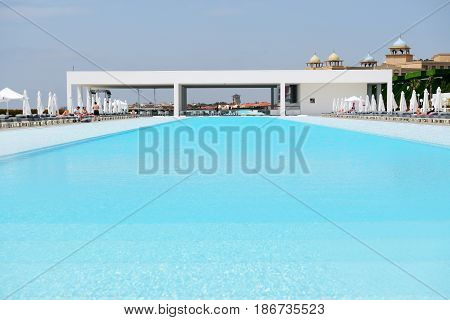 ANTALYA TURKEY - APRIL 22: The swimming pool at modern luxury hotel and tourists are on vacation on April 22 2014 in Antalya Turkey.
