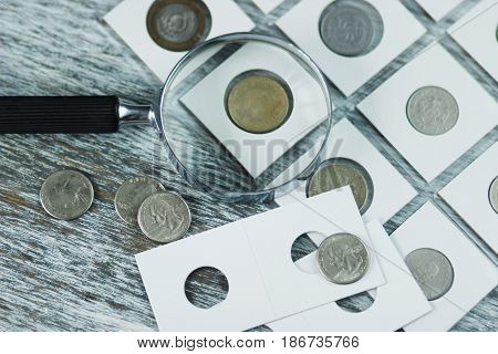 Page With Collector's Coins In The Pockets, And A Magnifying Glass