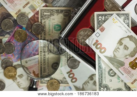 Ukrainian hryvnia and American's dollars with magnifying glass soft focus background