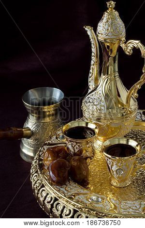 Still life with Traditional golden Arabic coffee set with dallah coffee pot and dates. Dark background. Vertical photo