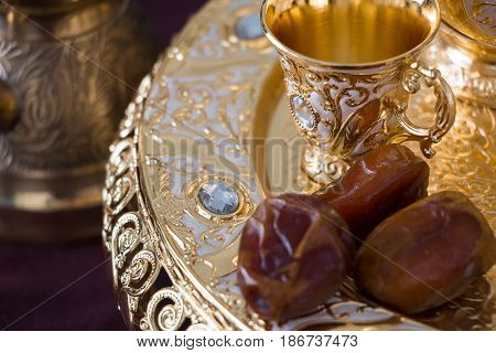 Still life with traditional golden arabic coffee set with dallah coffee pot (jezva) cup and dates. Dark background. Horizontal photo