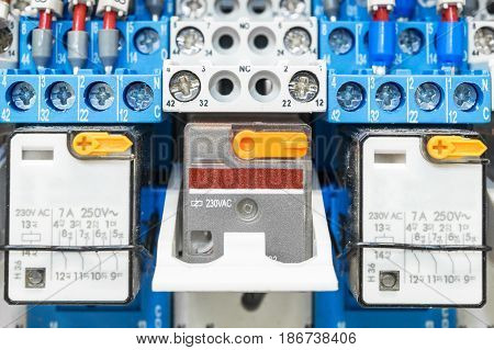 Some electrical relay is mounted on the mounting panel. Relays inserted in the base or socket. To the relay wires connected with the terminals and marking.