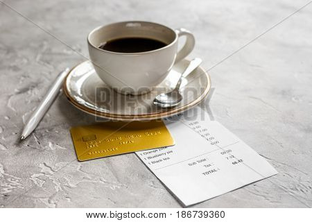 cup of coffee and receipt bill for payment by credit card on stone table background