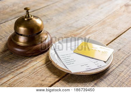 credit card for paying, waiter ring and check on cafe rustic wooden desk background