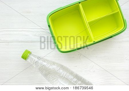 school lunch set with bottle of water and lunchbox on white table background top view mock up
