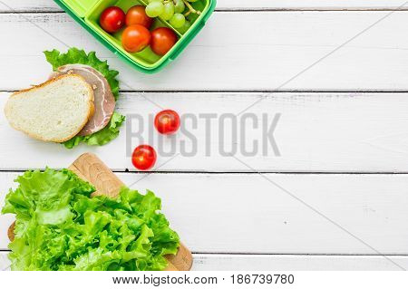 homemade lunch with lettuce, grape and sandwich in green lunchbox on white wooden table background top view mockup