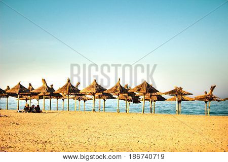 Beach With Straw Umbrellas And A Group Of People