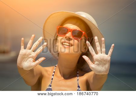 Sun protection cream on female hands. Safe tanning concept.