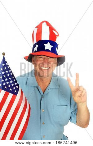 A handsome patriotic man wears an American Flag Hat, holds an American Flag and gives the Peace sign. Isolated on white. Room for text.