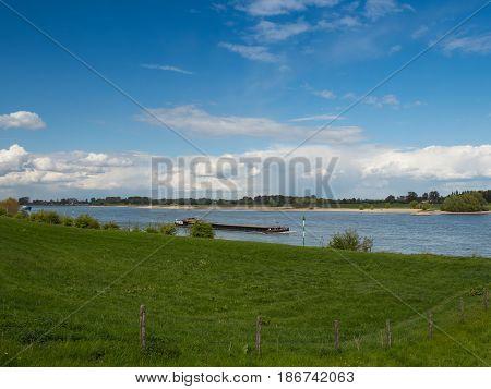 Ship drives the Rhine upstream Grieth Kalkar Germany
