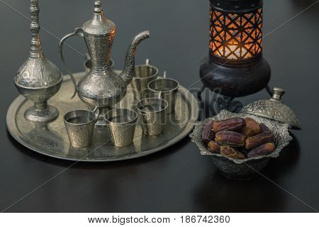 Dry dates and zam zam water cups with lantern on brown table