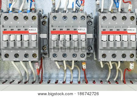 On the artboard mounted three electric contactor with auxiliary contacts. The contactors connected wires with ferrules and marking.