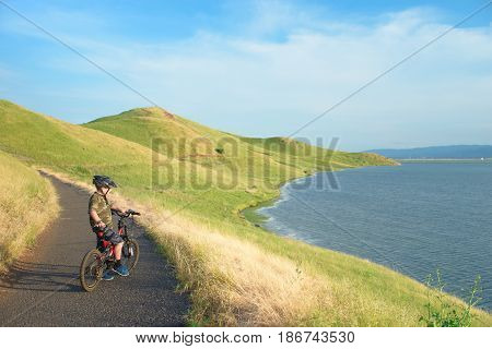 Happy boy riding his bike in the hills, enjoying sunny day, beautiful trail winding ahead through the bay.