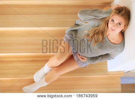 Beautiful young pregnant woman sits on the steps of a wooden ladder.