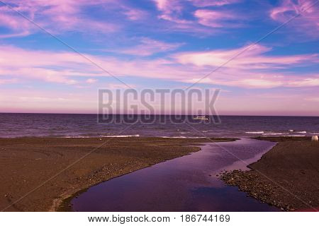Sunset view. Beautiful sunset beach. Mediterranean sea, river and yacht. Estepona city, Costa del Sol, Andalusia, Spain.