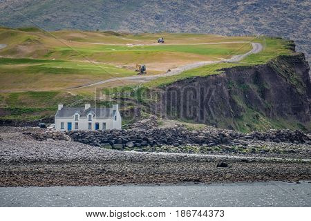 House on the rocky coast as seen from the Ballingskelligs Bay Beach in Waterville, County Kerry, Ireland