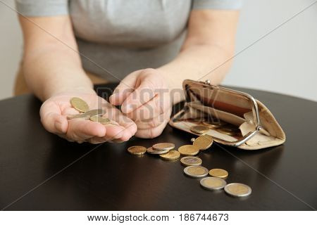 Senior woman counting coins while sitting at table, closeup. Poverty concept