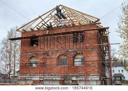 Workers are installing rafters on the roof of a brick house, standing on scaffolding