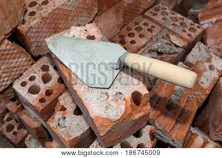 An old building tool, a trowel lying on a pile of red bricks