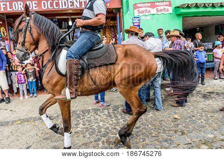 San Juan del Obispo, Guatemala - June 12 2016: Close up of horseback cowboy riding in horse street parade in village near Antigua, Guatemala