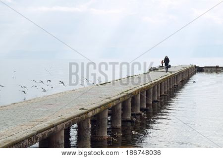 OHRID, MACEDONIA - MARCH 12, 2017: Woman walks on the pier of Ohrid lake, purposely blurred, selective focus on foreground