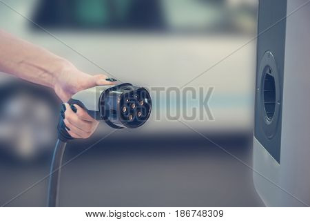 Female hand holding electric vehicle charger. Electric cars concept.