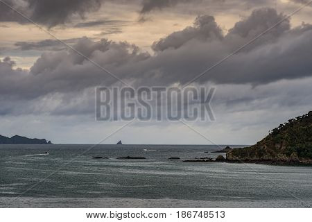 Bay of Islands New Zealand - March 7 2017: A major cyclone is building up over Pacific Ocean and the entrance to Paihia harbor. Cloudscape rocks on boths sides and dark water with a couple of boats