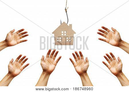 Hands reaching out for a house on a fish hook / Risks and negative sides of buying a house concept