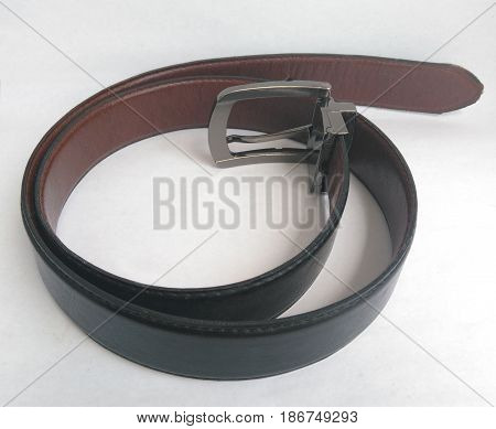 Closeup of man's fastened black leather pants belt shot on white
