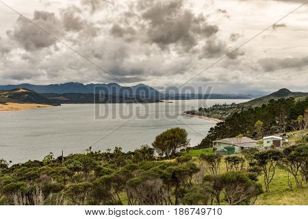 Bay of Islands New Zealand - March 7 2017: Opononi town on shore of Hokianga Harbour seen from Ti Pikinga Reserve. Wide shot of mountains the Hokianga River bush country all under heavy cloudscape