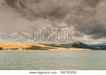Bay of Islands New Zealand - March 7 2017: Exit to Tasman Sea from Hokianga Harbour shows large dune under heavy cloudscape because of approaching cyclone.