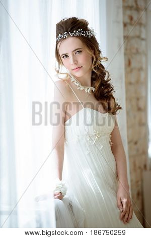 Brunette bride in fashion white wedding dress with makeup. Wedding day of bride in bridal gown. Beauty woman in veil. Fashion brunette model indoors. Beauty portrait of model in white bridal dress