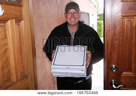 Pizza Delivery Man. A Handsome and friendly Pizza Delivery Man brings Hot Fresh Pizza to your Home or office for Dinner or Lunch.