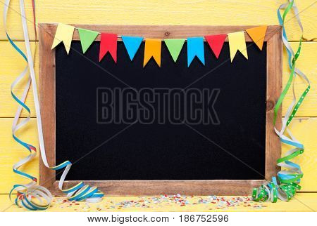 Chalkboard With Copy Space For Advertisement. Party Decoration Like Streamer, Confetti And Bunting Flags. Yellow Wooden Background With Vintage, Retro Or Rustic Syle