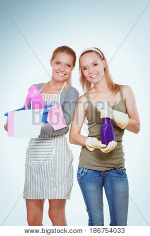 Two women is cleaning something with wisp and spray attentively