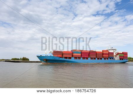 Dramatic view of a fully loaded cargo container ship returning to port on the Savannah River in Georgia. Copy space in sky if needed.