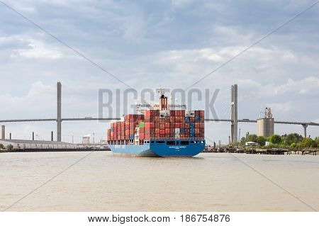 Savannah GA - March 27 2017: Container ship approaching the Talmadge Memorial Bridge on the Savannah River as it enters the Port of Savanna in Georgia. Savannah is one of the largest container ports in North America.
