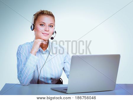 Portrait of beautiful business woman working at her desk with headset and laptop