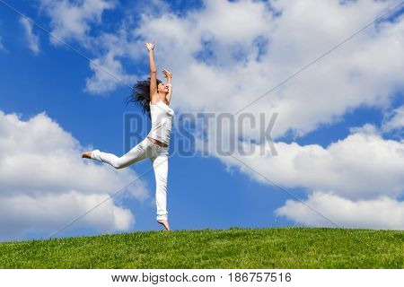 Happy young woman jumping on green grass. Landscape of grass field on bright sunny day. Nature beauty background, blue cloudy sky and summer green meadow. Outdoor lifestyle. People freedom concept