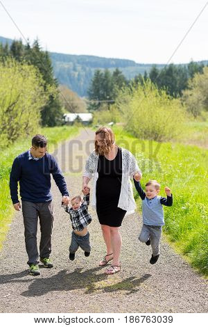 Family photo of a mother, father, and their two kid boys outdoors in a natural field in Oregon.