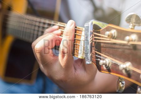 closeup of man's hands playing acoustic guitar soft vintage style