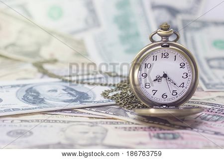 Classic pocket watch on dollar banknote concept and idea of time value and money business and finance concepts.
