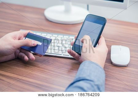 hands holding credit card and a typing on the phone making online purchase. Copyspace on phone screen. Office concept