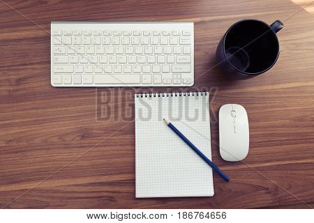 Top view of office wooden table with stationary. Office desk table with keyboard, notepad, pencil and mouth. Copyspace